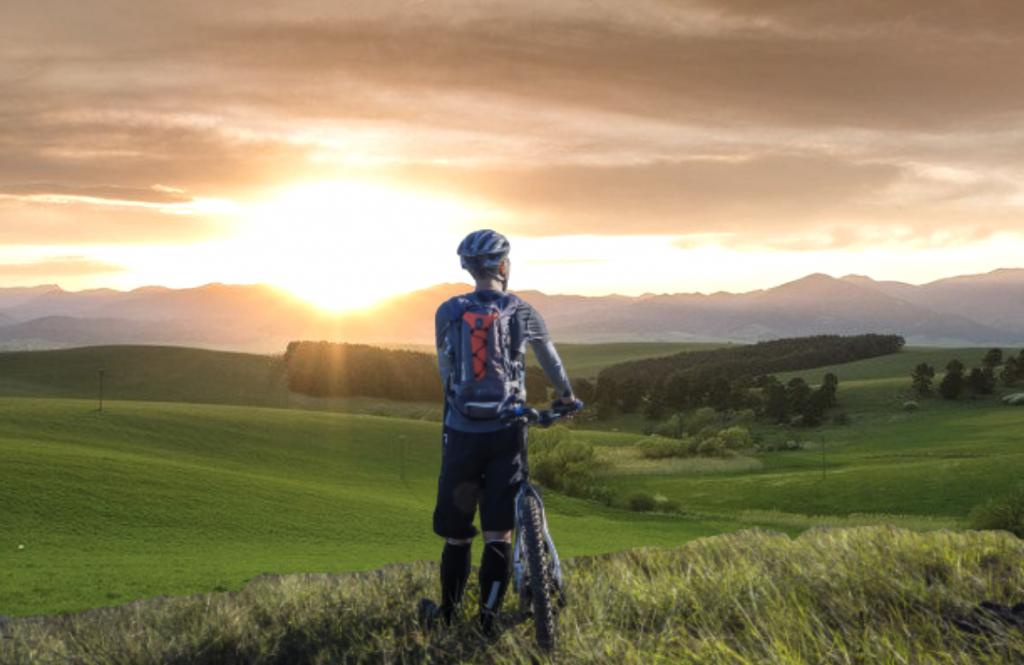 Maastoyöräiljä auringonlaskussa